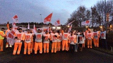 Menschengruppe von Müllwerkern in Streikwesten