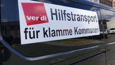 Schwarzes Fahrzeug mit Aufkleber. Darauf steht: ver.di Hilfstransport für klamme Kommunen